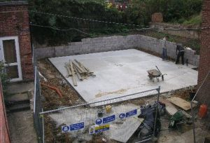 Finishing the concrete raft behind the museum.